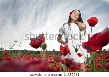 Pretty woman in poppy flowers - stock photo