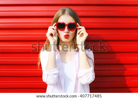 Pretty woman in red sunglasses blowing lips kiss over colorful background - stock photo