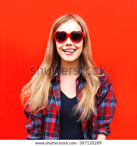 Pretty woman in red sunglasses having fun over colorful background - stock photo