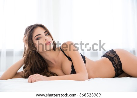 Pretty woman in sexy lingerie lying on the bed and looking at camera - stock photo