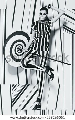 pretty woman in striped top with umbrella on striped background in studio - stock photo