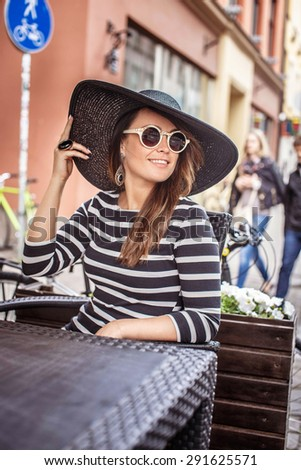 Pretty woman in summer hat and sunglasses at the table in summer cafe.