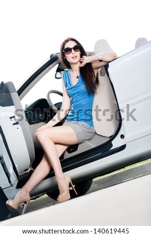 Pretty woman in sunglasses sits in the car with side door opened - stock photo