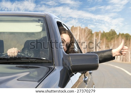 pretty woman in the car and shows ok sign - stock photo