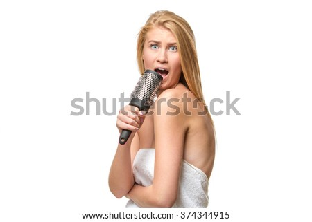 Pretty woman in towel singing using comb   - stock photo