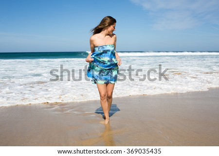 Pretty woman in turquoise dress on the beach