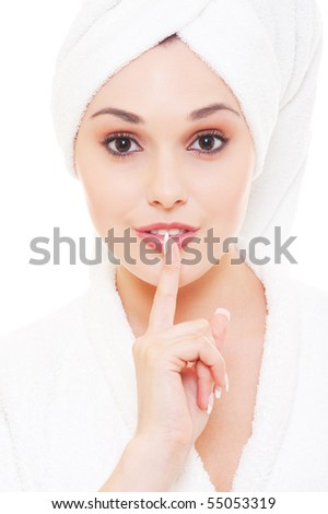 pretty woman in white towel making silence sign - stock photo