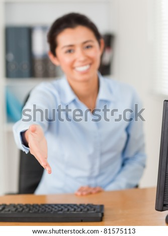 Pretty woman inviting somebody to seat while looking at the camera at the office - stock photo