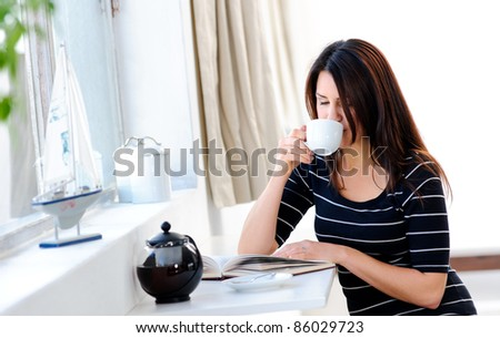 Pretty woman is contented with her morning coffee - stock photo