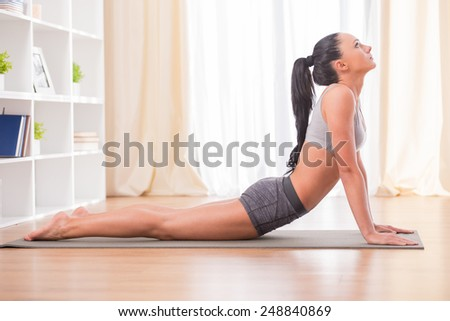 Pretty woman is doing fitness at home on her living room floor. Fitness, workout, healthy living and diet concept. - stock photo