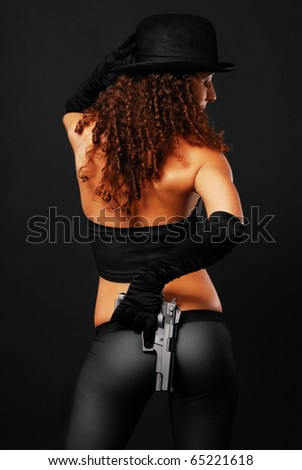 Pretty woman is hiding a handgun behind her back on the dark background. Sexy gangster is wearing tight trousers, a stripy top, long gloves and a black hat. She is photographed from the rear. - stock photo