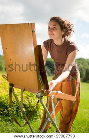 Pretty woman is painting. Open air session. - stock photo
