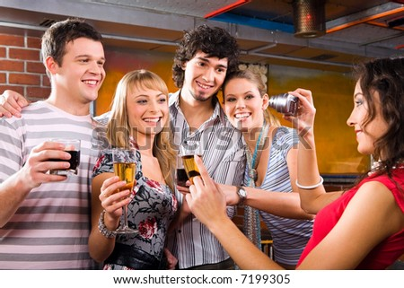 Pretty woman is photographing her friends in a night-club - stock photo