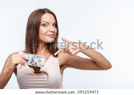 Pretty woman is pointing her index finger at dollar. She is holding it in her right hand. The girl is gently smiling. Isolated on background and there is copy space in left side - stock photo