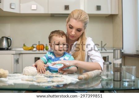 Pretty woman is preparing dough with her kid. They are baking with interest. The mom is sitting at the table and holding her son on her knees