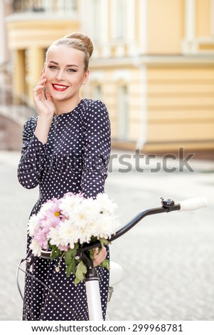 Pretty woman is riding the bicycle in town. She is touching her face gently and smiling. The lady is looking at the camera with pleasure. Copy space in right side - stock photo