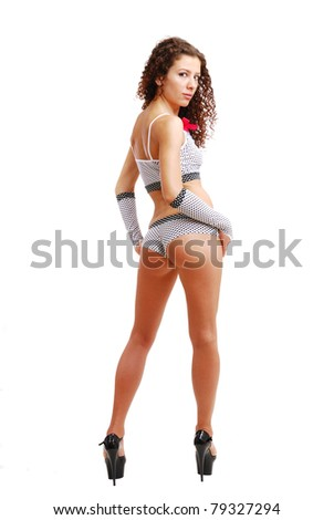 Pretty woman is standing back and turning. She is looking at camera over shoulder. Her legs is on high stiletto heels. The stripper is wearing sexy shorts and top. - stock photo