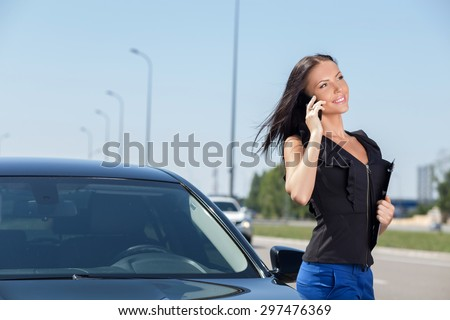 Pretty woman is standing near her car on the road. She is communicating on the mobile phone and smiling. The girl is holding a folder - stock photo