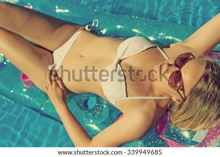 Pretty woman is sunbathing in swimming pool. - stock photo