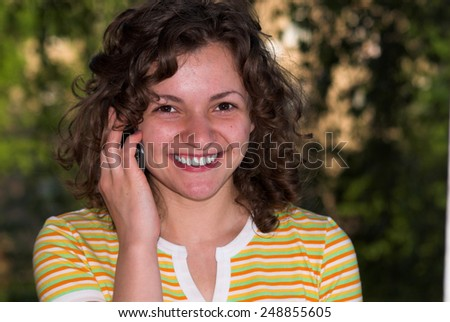 Pretty woman is talking via telephone in the morning - stock photo