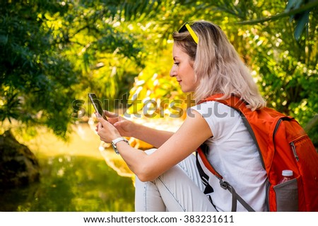 Pretty woman is using smartphone resting at the river in a forest - stock photo