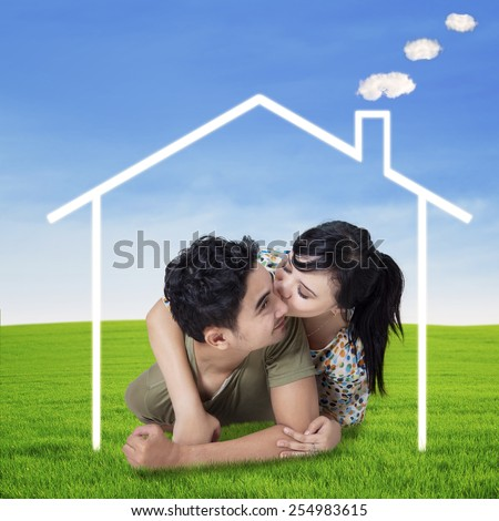 Pretty woman kiss her boyfriend on the grass under a dream house at field