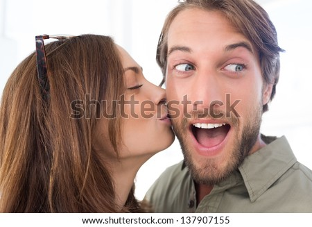 Pretty woman kissing man with beard on the cheek - stock photo
