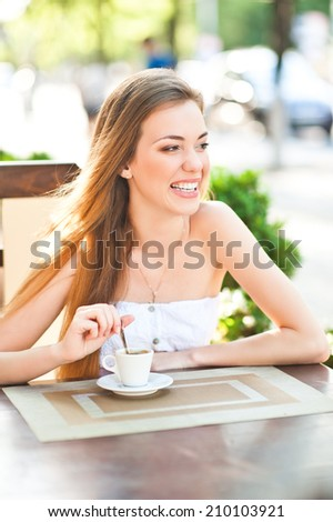 Pretty woman laughing with cup of coffee looks into the distance