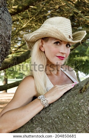 Pretty woman leaning on large branch of pine tree wearing a cowgirl hat. - stock photo