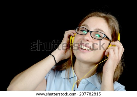 pretty woman listening to music with a headphone on black background