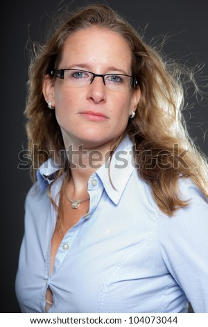 Pretty woman long blond hair wearing glasses and light blue shirt. Isolated on grey background. Studio shot.