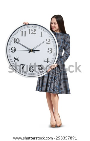 pretty woman looking at big clock and smiling. isolated on white background - stock photo
