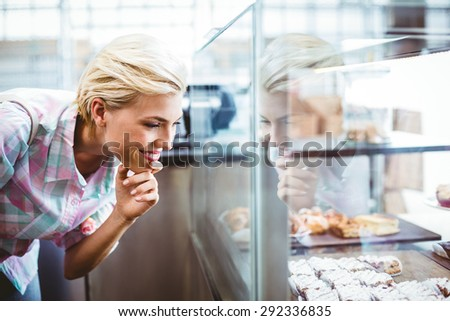 Pretty woman looking at cup cakes at the bakery - stock photo