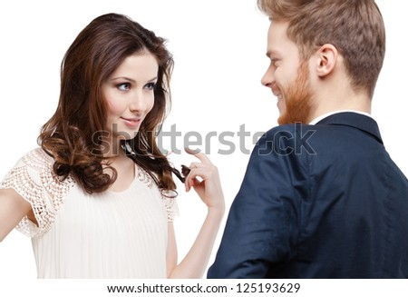 Pretty woman looks slily at her boyfriend and touches her hair, isolated on white - stock photo