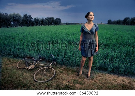 pretty woman lost with her bike in the country - stock photo
