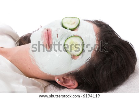 Pretty woman lying and relaxing with a facial mask - stock photo