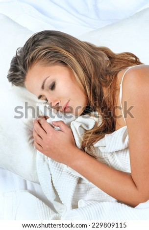 Pretty woman lying down on her bed at home waking up in the morning - stock photo