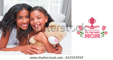 Pretty woman lying on bed with her daughter smiling at camera against mothers day greeting - stock photo