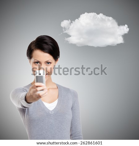 Pretty woman making a photo with mobile phone, isolated on grey background with cloud - stock photo