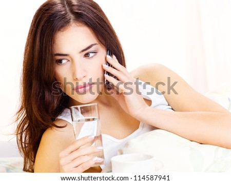 Pretty woman making phone call and holding glass of water in bed