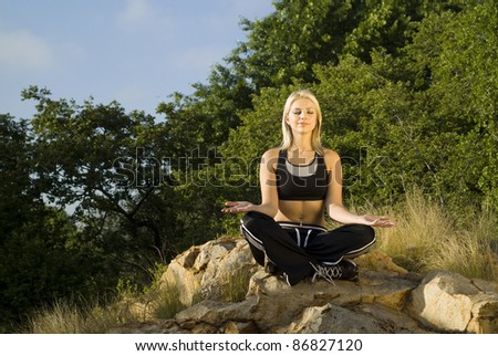 Pretty woman meditating on rock eyes closed with gold light reflector - stock photo
