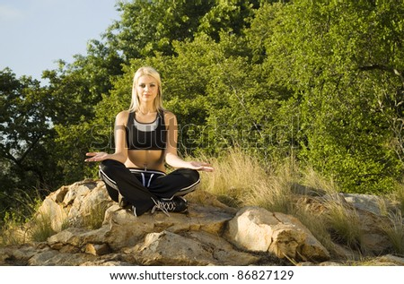 Pretty woman meditating on rock open hands with gold light reflector - stock photo