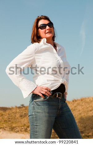 Pretty woman middle aged enjoying outdoors. Clear sunny spring day with blue sky. - stock photo