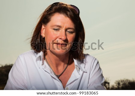 Pretty woman middle aged reading a book and enjoying outdoors. Clear sunny spring day with blue sky. - stock photo