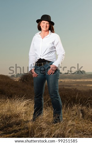 Pretty woman middle aged wearing a hat enjoying outdoors. Clear sunny spring day with blue sky. - stock photo