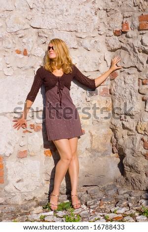 Pretty woman near the ancient brick wall - stock photo