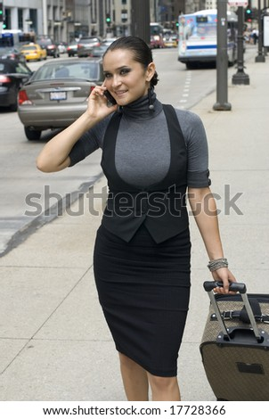Pretty woman on cell phone while  waiting for a taxicab - stock photo