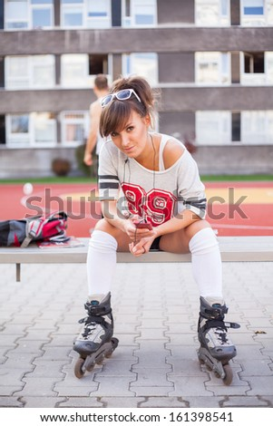 Pretty woman on rollerblades sitting on bench. - stock photo