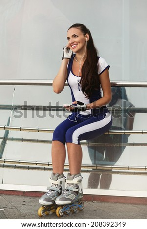 Pretty woman on rollerblades sitting with mobile phone. - stock photo