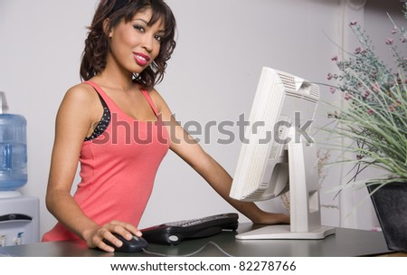 Pretty woman on the computer browsing the internet hand on mouse - stock photo